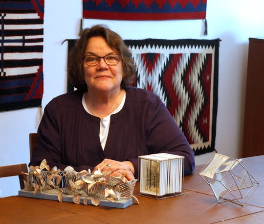 Pam Wright with three examples of deconstructed books she created with the words of prisoners from the Dutchess County Jail at her home in Rhinebeck on March 7 2019.
