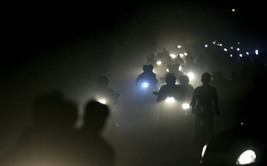 In this Friday, Nov. 10, 2017 file photo, motorists ride through a thick blanket of smog and dust on the outskirts of New Delhi, India., with microscopic particles spiking at times to 75 times the level considered safe by the World Health Organization. According to a scientific report from the United Nations released on Wednesday, March 13, 2019, climate change, a global major extinction of animals and plants, a human population soaring toward 10 billion, degraded land, polluted air, and plastics, pesticides and hormone-changing chemicals in the water are making the planet an increasing unhealthy place for people.
