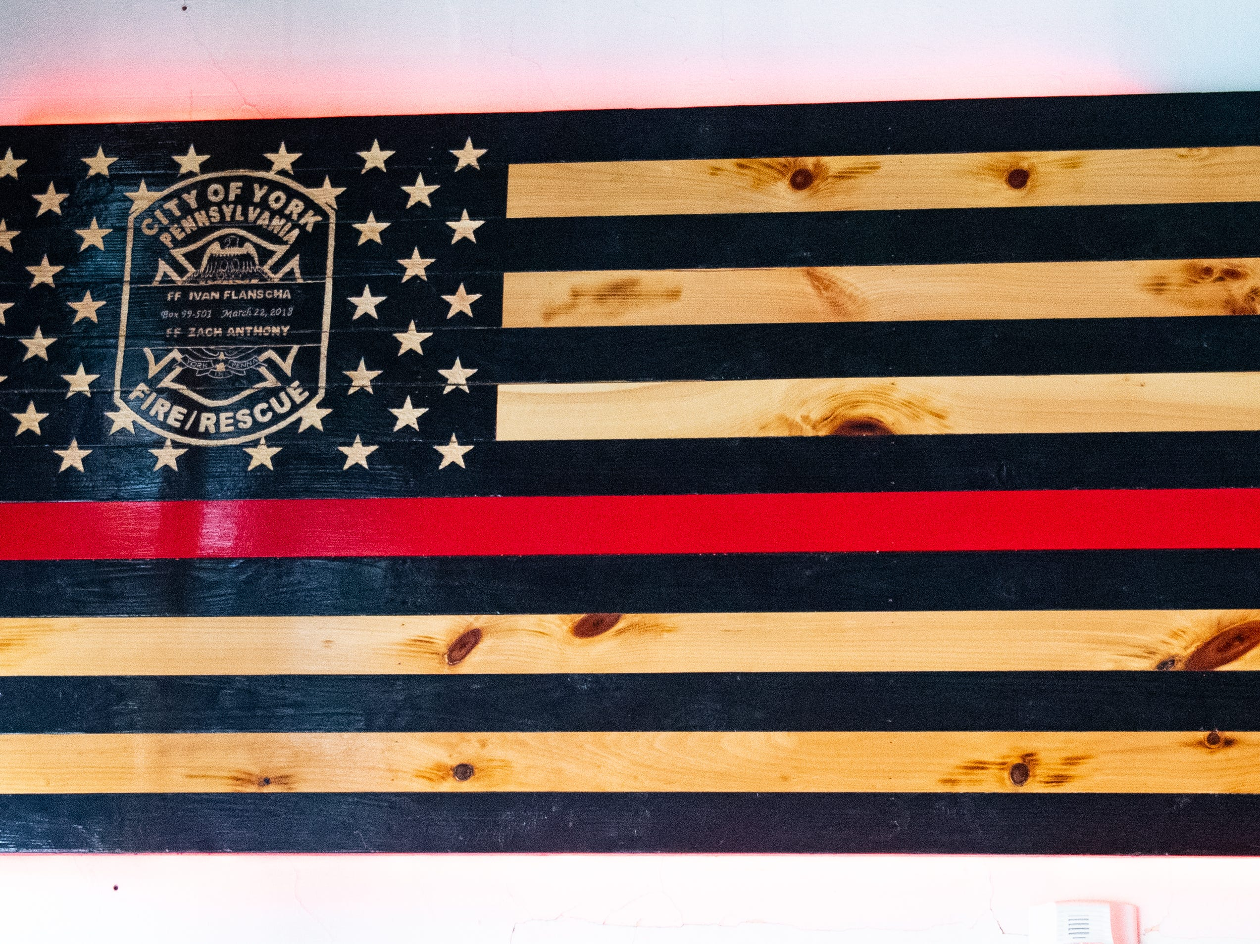 This custom made flag hangs next to a fire poll in the fire engine garage. It was a gift from the community and commemorates both firefighters lost last year, March 12, 2019.