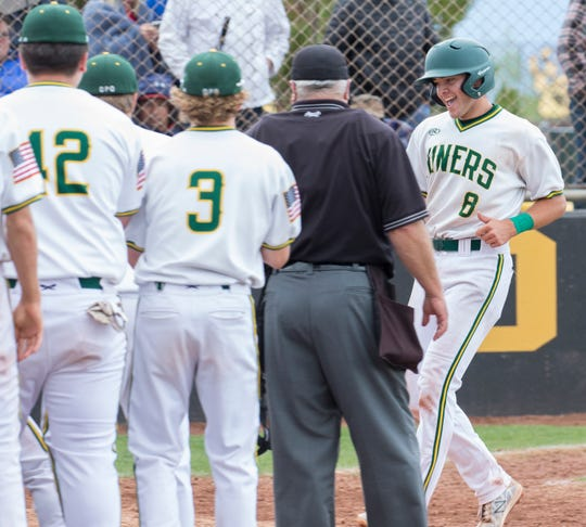 Manogue's CJ Hires is congratulated by teammates after hitting a home run against Reno in the  4A Northern Regional Baseball Championship on  May 12, 2018.