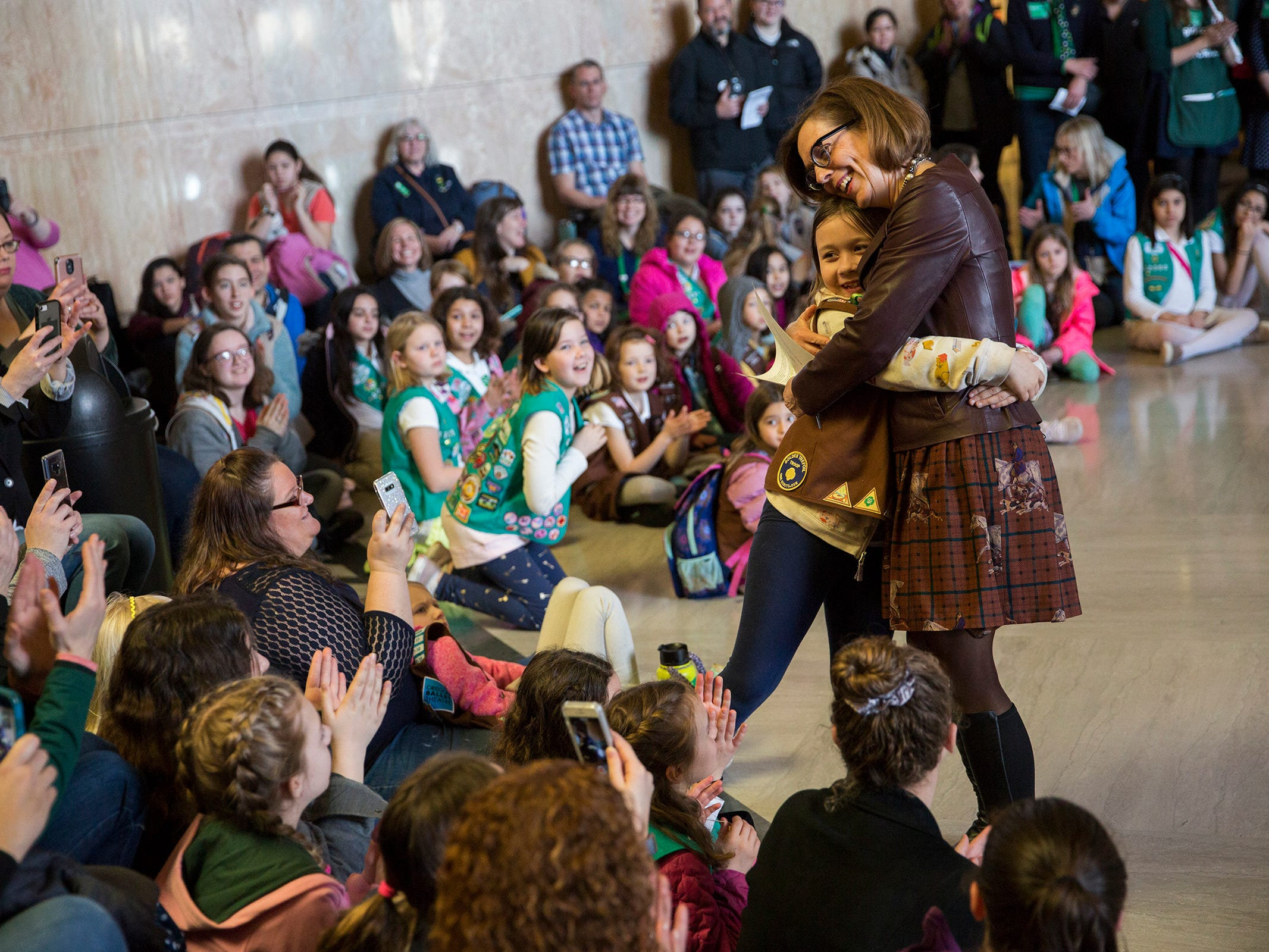 Girl Scout Josie Weishar, of Eugene, hugs Gov. Kate Brown during Girl Scout Leadership Day at the Oregon State Capitol in Salem March 12, 2019.