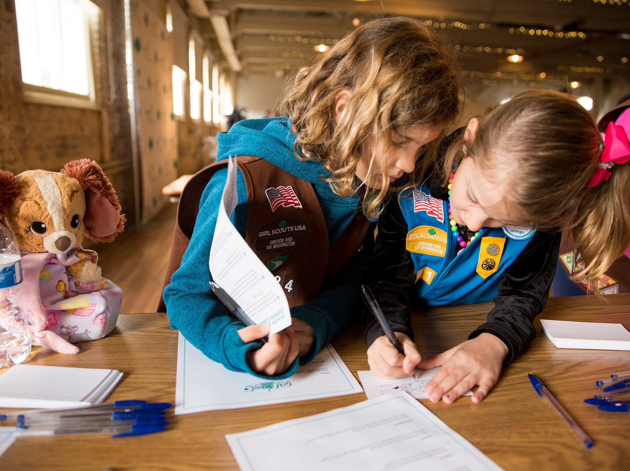 Sisters Charlotte Ferschweiler, 6, and Ava Ferschweiler, 8, of Milwaukee, write down interview questions to ask other girls during Girl Scout Leadership Day at the Willamette Heritage Center in Salem March 12, 2019.