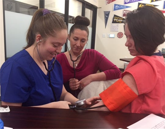 Oregon Connections Academy students Sidney Kincaid (left) and Mikayla Wood (right), supervised by instructor Anika Miller, practice taking blood pressure as part of their Medical Sciences Pathway program at the school.