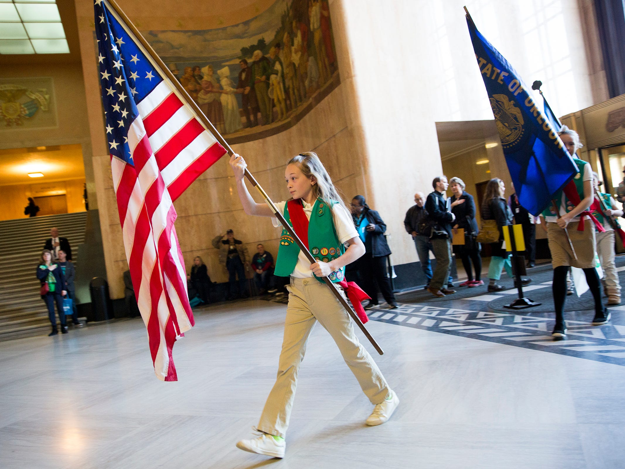 Addison Peterson, of Albany, carries in a flag before reciting the pledge of allegiance during Girl Scout Leadership Day at the Oregon State Capitol in Salem March 12, 2019.