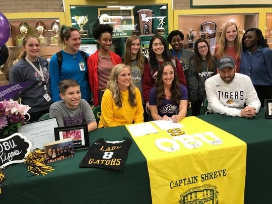 Captain Shreve's Abigail Roberts prepares to sign scholarship papers to Ouachita Baptist Wednesday with her family and Lady Gator teammates surrounding her.