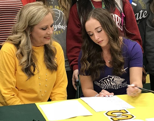 Captain Shreve's Abigail Roberts signs volleyball scholarship papers to OBU Wednesday while her mother, Tara, looks on. Roberts becomes the first Lady Gator volleyball player to earn an athletic scholarship.