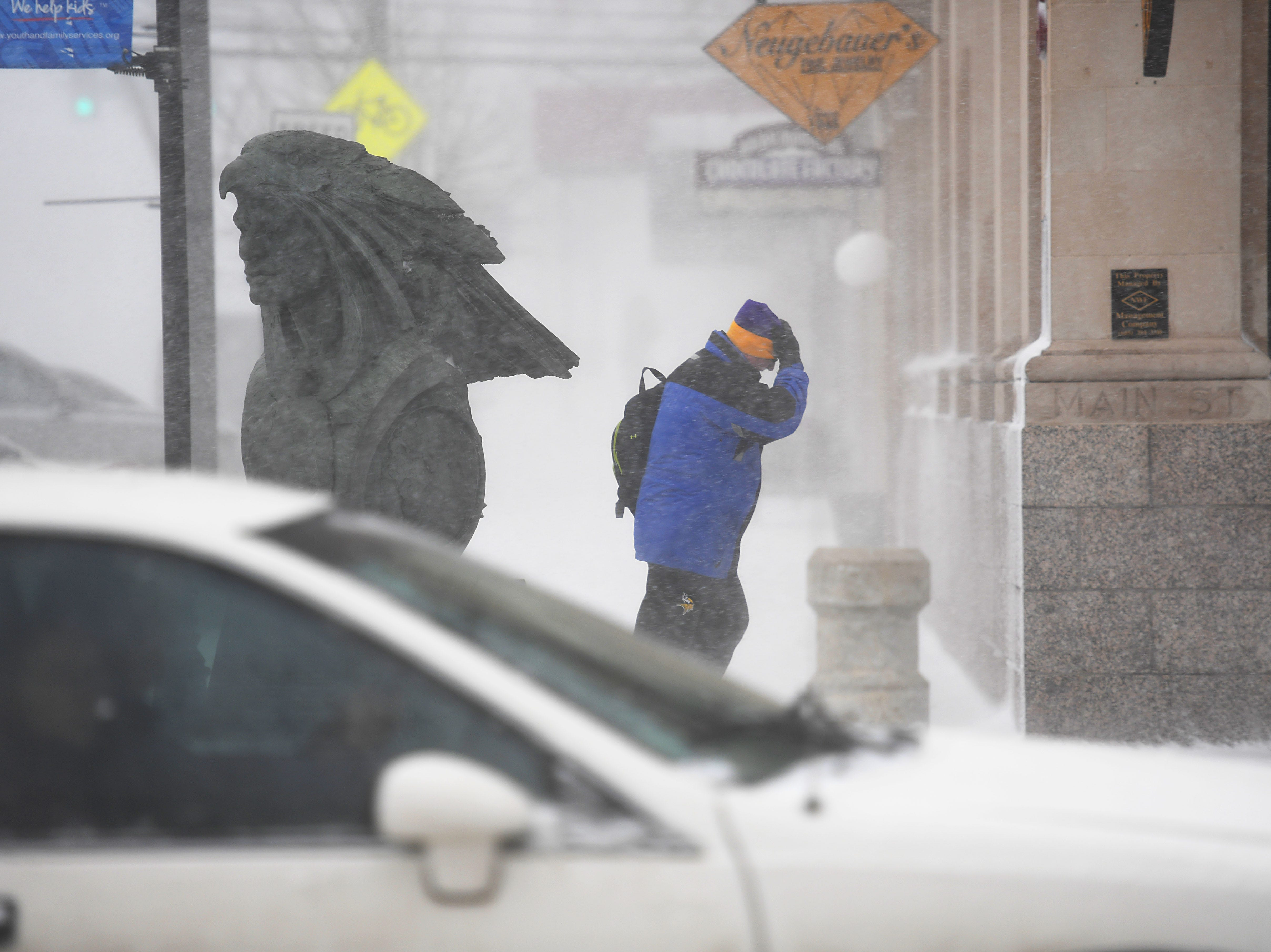 A pedestrian makes their way through downtown during a blizzard in Rapid City Wednesday, March 13, in Rapid City, S.D.