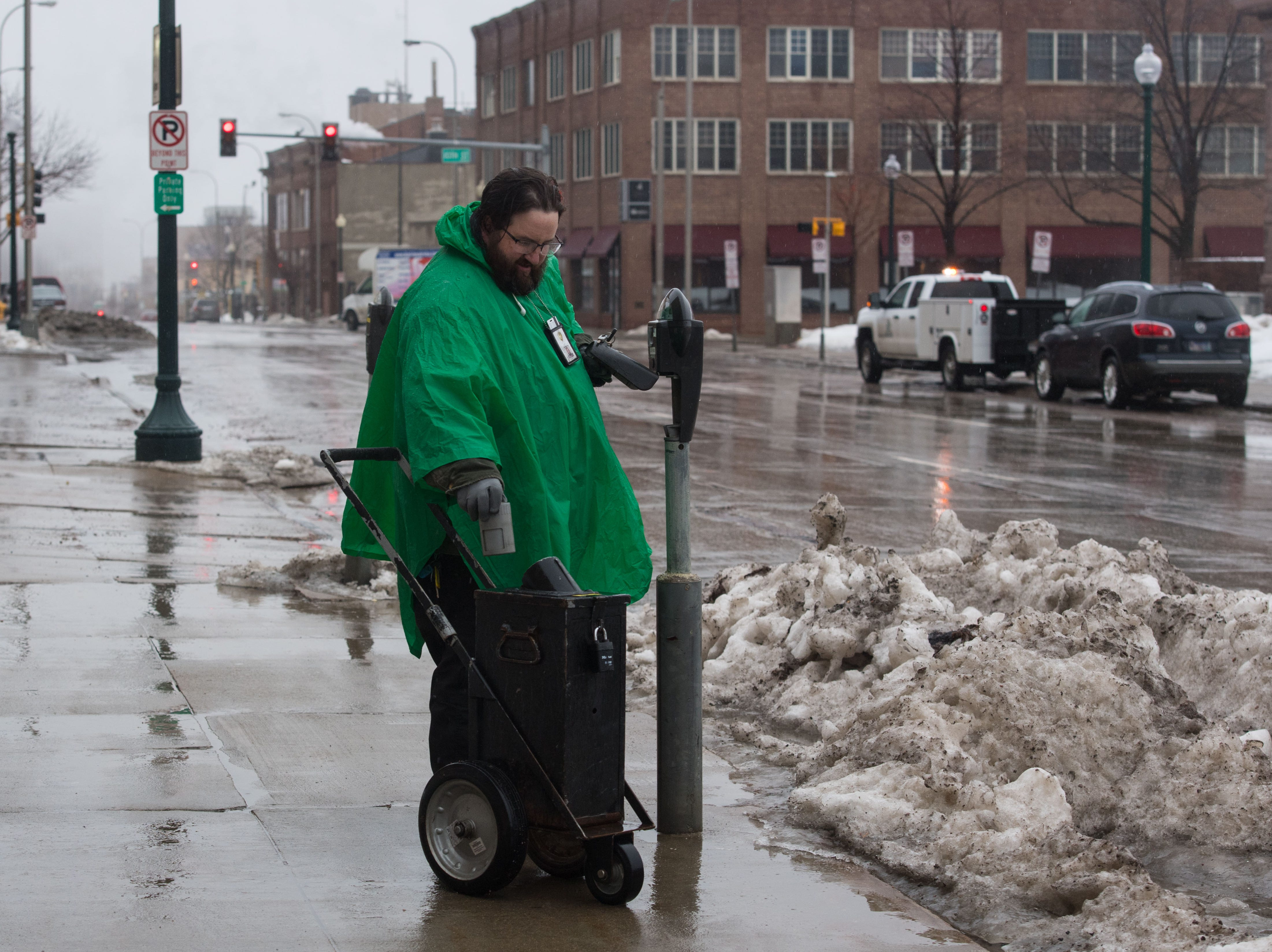 Toby Bartlett collects money from the meters in the rain in downtown Sioux Falls, S.D., Wednesday, March 13, 2019.