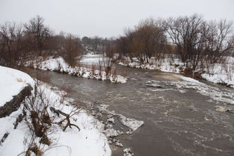 The pedestrian bridge at Dunham Park that sits over Skunk Creek was destroyed on Thursday when rushing water carried it down river.