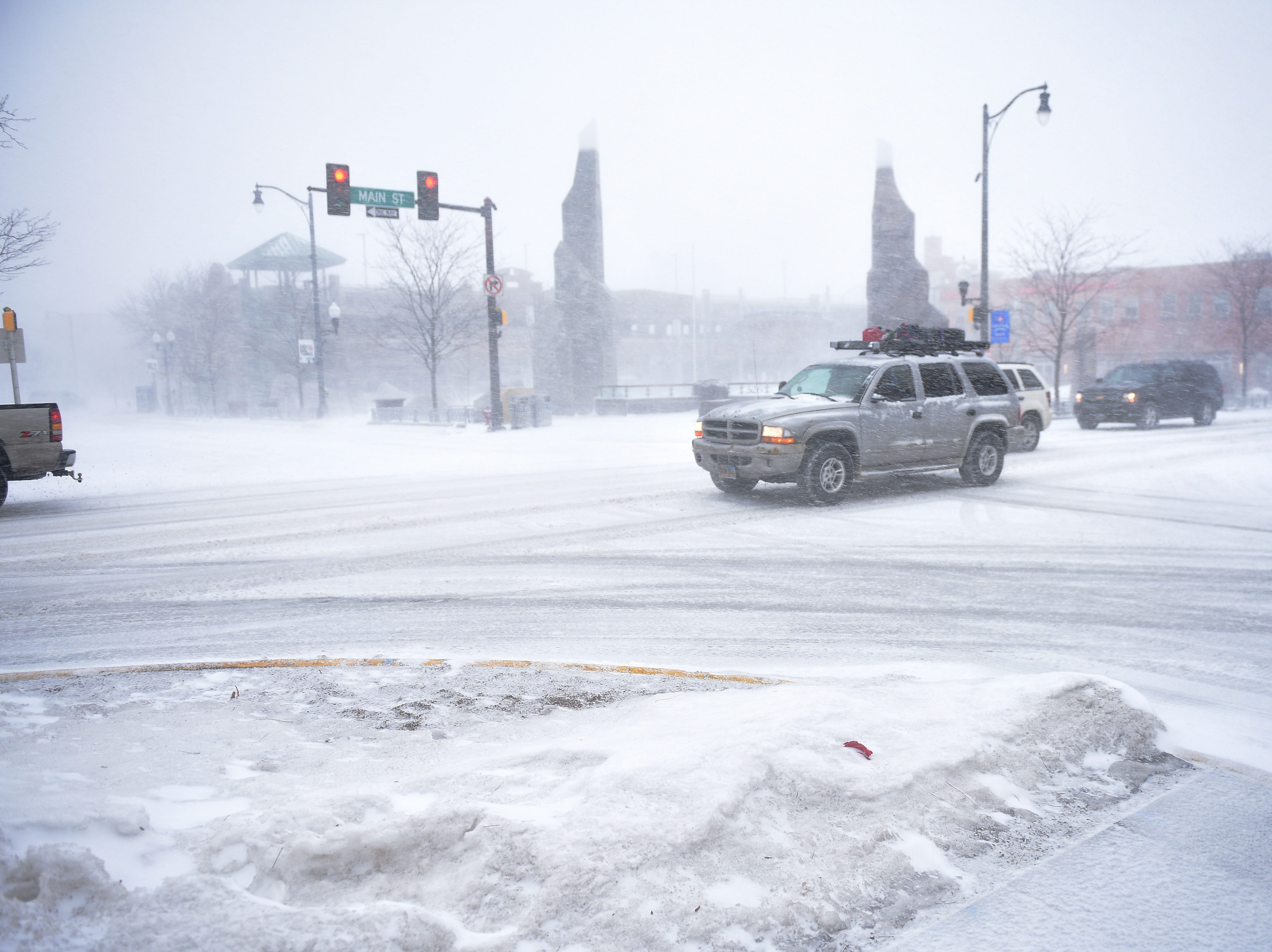 Drivers slowly make their way around downtown during a blizzard in Rapid City Wednesday, March 13, in Rapid City, S.D.