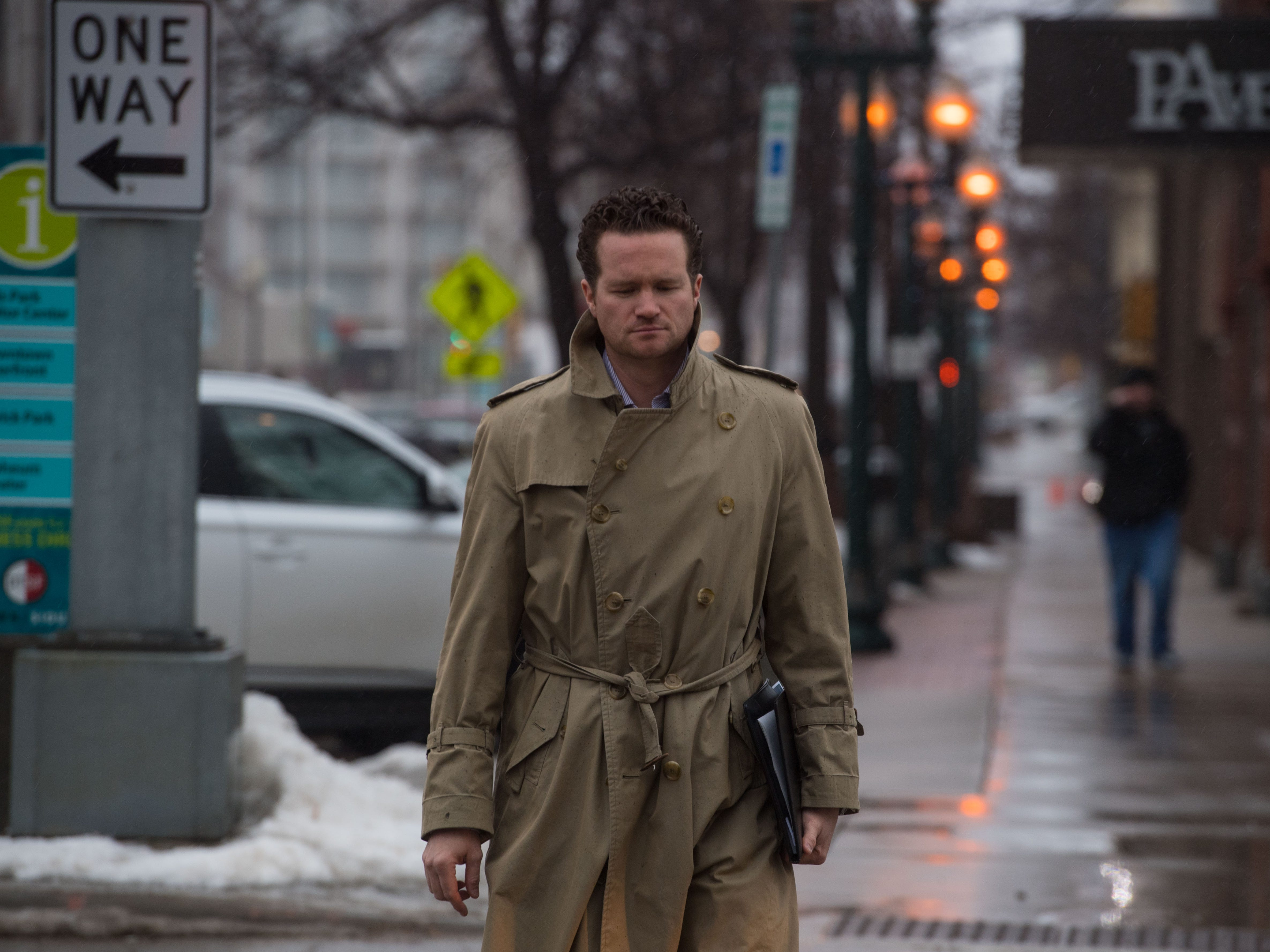 Jon Kirby walks in the rain in downtown Sioux Falls, S.D., Wednesday, March 13, 2019.