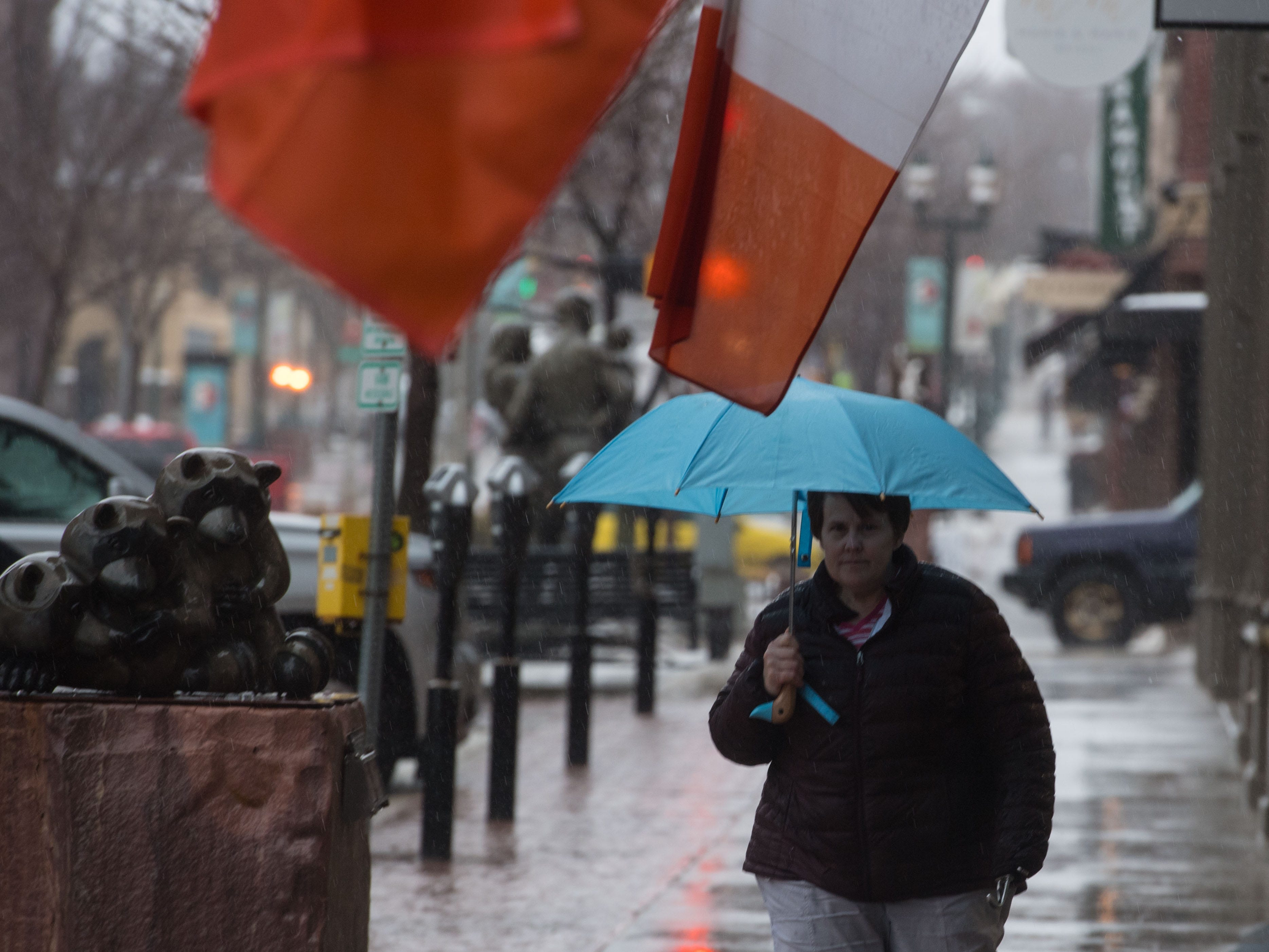 Robin Mills walks in the rain in downtown Sioux Falls, S.D., Wednesday, March 13, 2019.