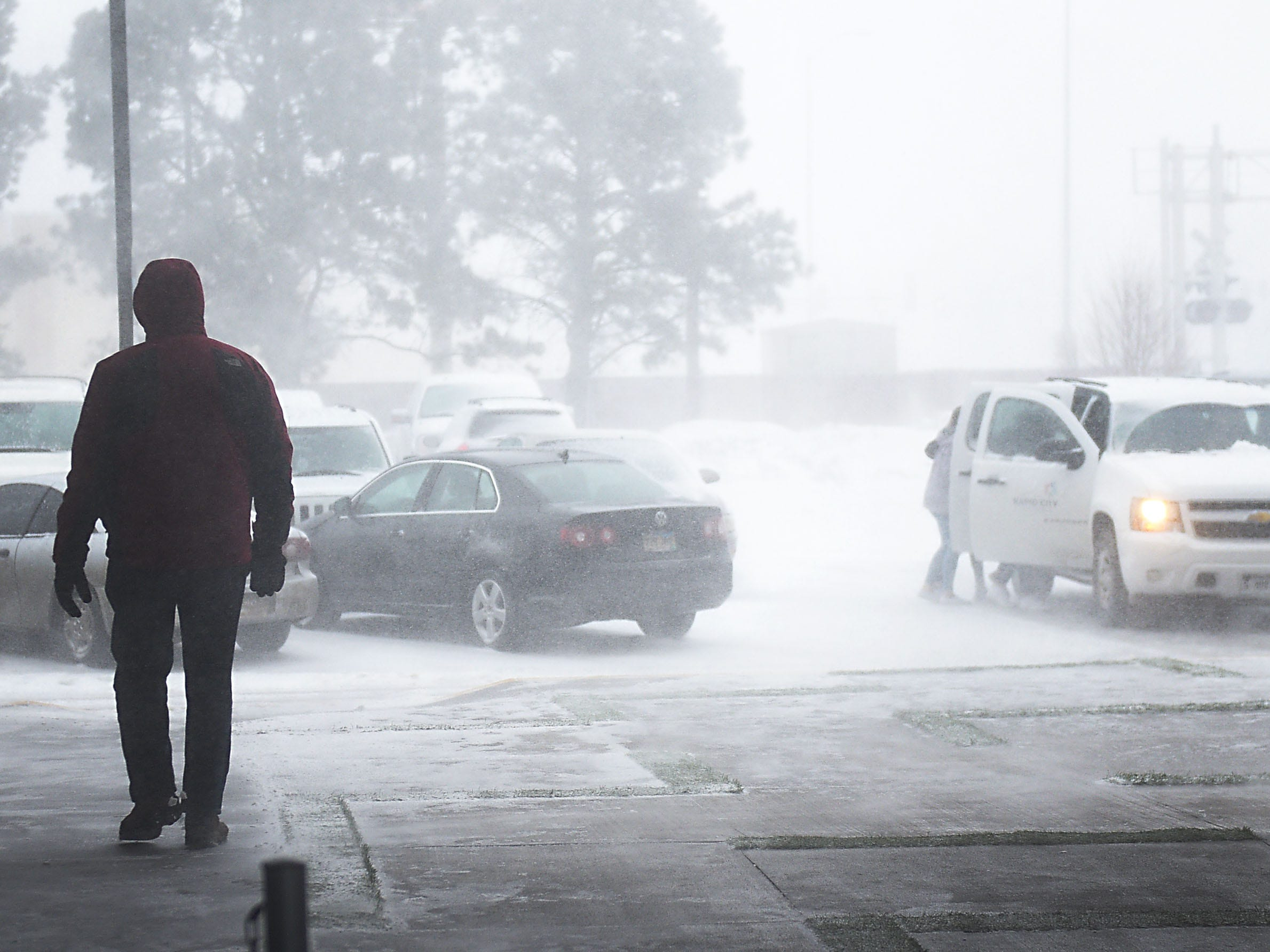 A pedestrian, left, walks to their car as a group of people, right, run to their vehicle during a blizzard in Rapid City Wednesday, March 13, in Rapid City, S.D.