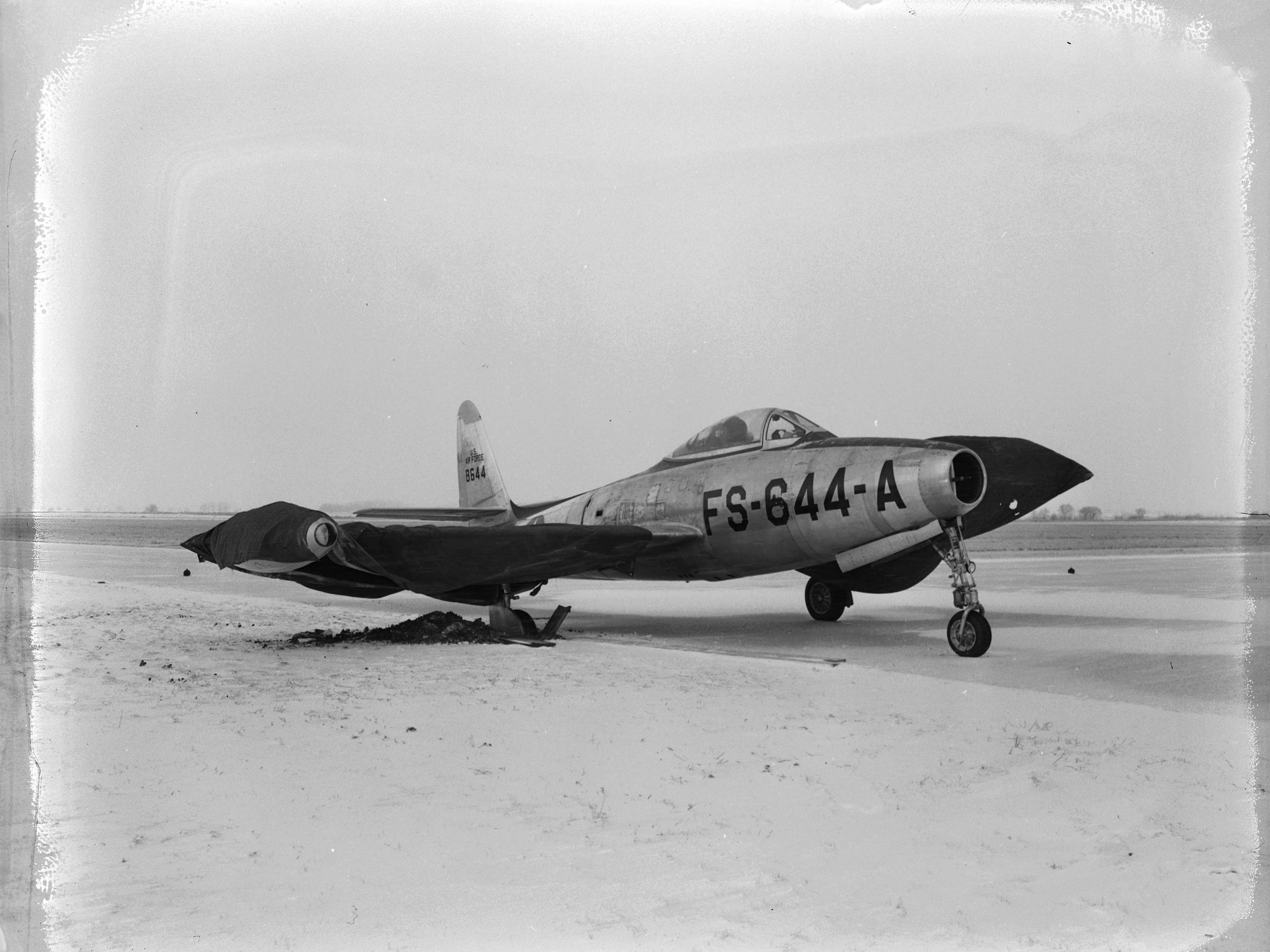"A heavy Army jet fighter plane which was bogged down in the mud ""Big Mo style"" after slipping off a concrete runway at municipal airport. The plane, piloted by Captain Lon Kappell, husband of Springfieldian Jean Lightfoot Kappell, finally was freed from its muddy bed, only after the Navy, remembering the Army's offer of 'assistance' in freeing the battleship Missouri, told Kappell it ""would be glad to help."" Published in the Leader & Press on March 13, 1950."