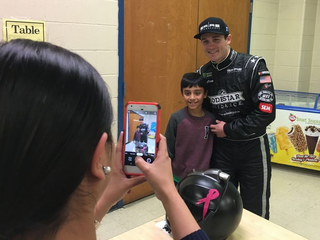 NASCAR driver Quin Houff took a photo with Clymore Elementary student Muizz Malik, 8, Tuesday night during the school's Reading Family Fun Night.