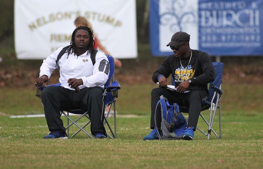 Rickards track coach Johnathan Butler (right) and his assistant watch action during the 2019 Jimmy Everett Invitational track meet at Lincoln.