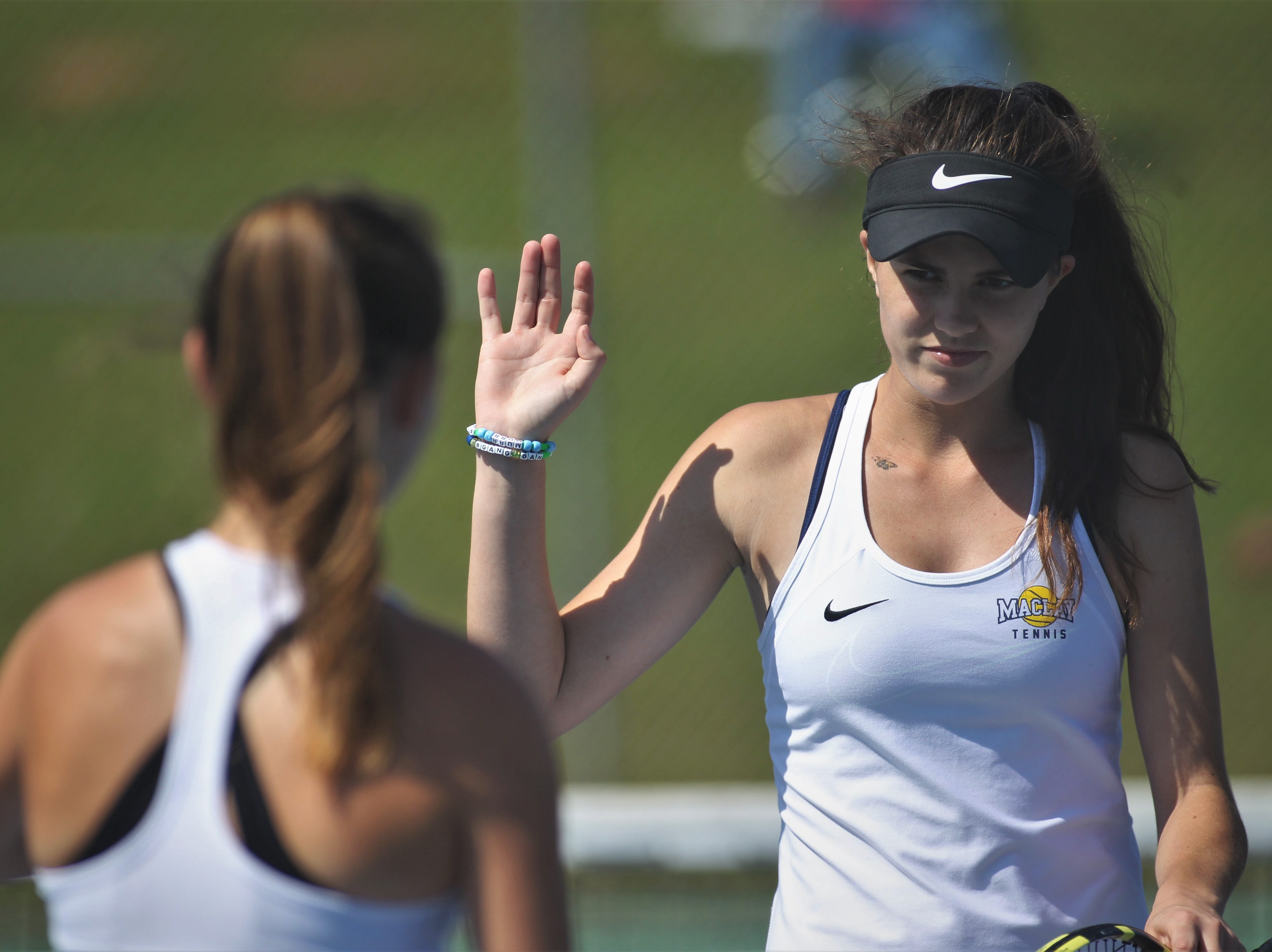 Maclay's Madison Perkins prepares to high five doubles partner Rachael Stockel after winning a point during the boys and girls tennis 2019 City Tournament at Tom Brown Park on March 12, 2019.