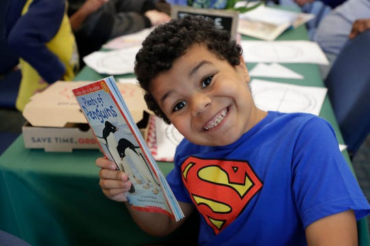 Isaiah Townsend, 7, poses for a photo with a book about penguins that he is enjoying on Wednesday, March 13, 2019. Pineview Elementary makes learning fun by doing a pizza themed 'book tasting' as one of the ways to get students excited about reading.