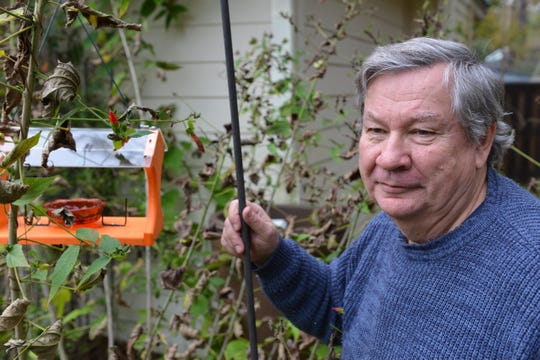 Rob Williams of Apalachee Audubon stands besides his Oriole feeder.