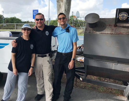 "Assistant to the Chief Lisa Scott, Officer Corey Lee and volunteer Travis Brockman get ready to fire up the grill to prepare lunch for volunteers at the third annual Love Thy Neighborhood event: ""Paint Me Beautiful"" in East Stuart."