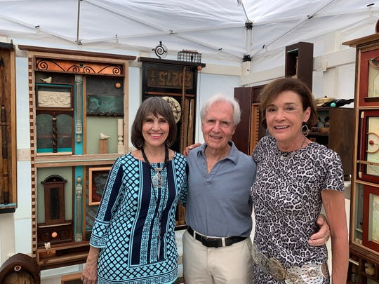 Joan Earnhart, left, George Paxton and Paulette Visceglia at Earnhart's booth at the 68th annual Under the Oaks art show March 10.