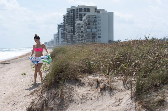 Alyxandrea Gorgone, of Fort Pierce, spends a windy afternoon with her friends Wednesday, March 13, 2019, at Dollman Park Beachside in St. Lucie County. The beach, suffering from erosion, is one of several St. Lucie County beaches denied $12 million in Federal Emergency Management Agency funding for Hurricane Irma repairs.