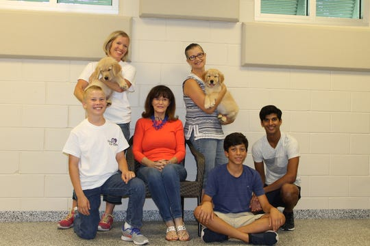 In 2017, Vero Beach philanthropist Kathi G. Schumann bought two Golden Retriever puppies that were trained by Dogs for Life for veterans in Vero Beach and Indian River County.  Pictured are, from left, Tyler Drinnon, Kristen Drinnon holding Good Girl, Kathi G. Schumann, Sheri Taylor holding Good Boy, Harry Taylor and Joe Taylor.