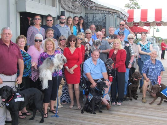 Kathi G. Schumann, standing, center in red, with members of Dogs for Life Inc. and their personal and service dogs at the 2017 Schumann Annual Christmas Party at the Ocean Grill in Vero Beach.