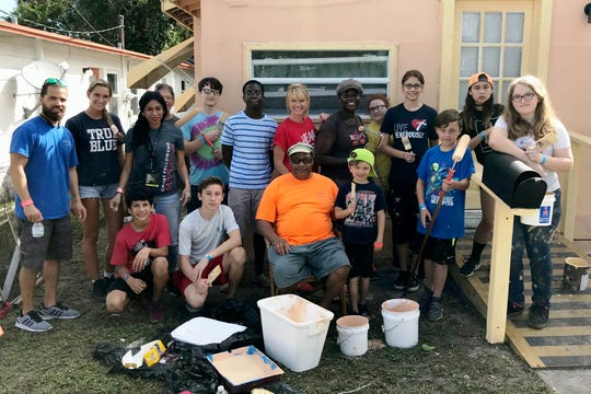 "Homeowner Isaac Love, seated, center, with volunteers from Christ Fellowship and First Baptist Churches in Stuart at the third annual Love Thy Neighborhood event: ""Paint Me Beautiful."""