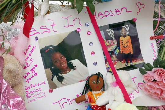 Photos adorn a large memorial to Trinity Love Jones, the 9-year-old girl whose body was found in a duffel bag along a suburban Los Angeles equestrian trail, in Hacienda Heights on Monday.
