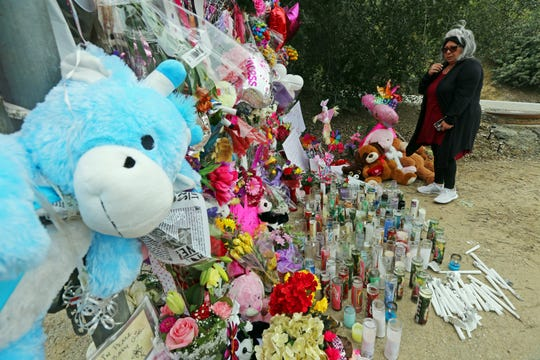 A woman crosses herself at a large memorial to Trinity Love Jones, the 9-year-old girl whose body was found in a duffel bag along an equestrian trail in Hacienda Heights.