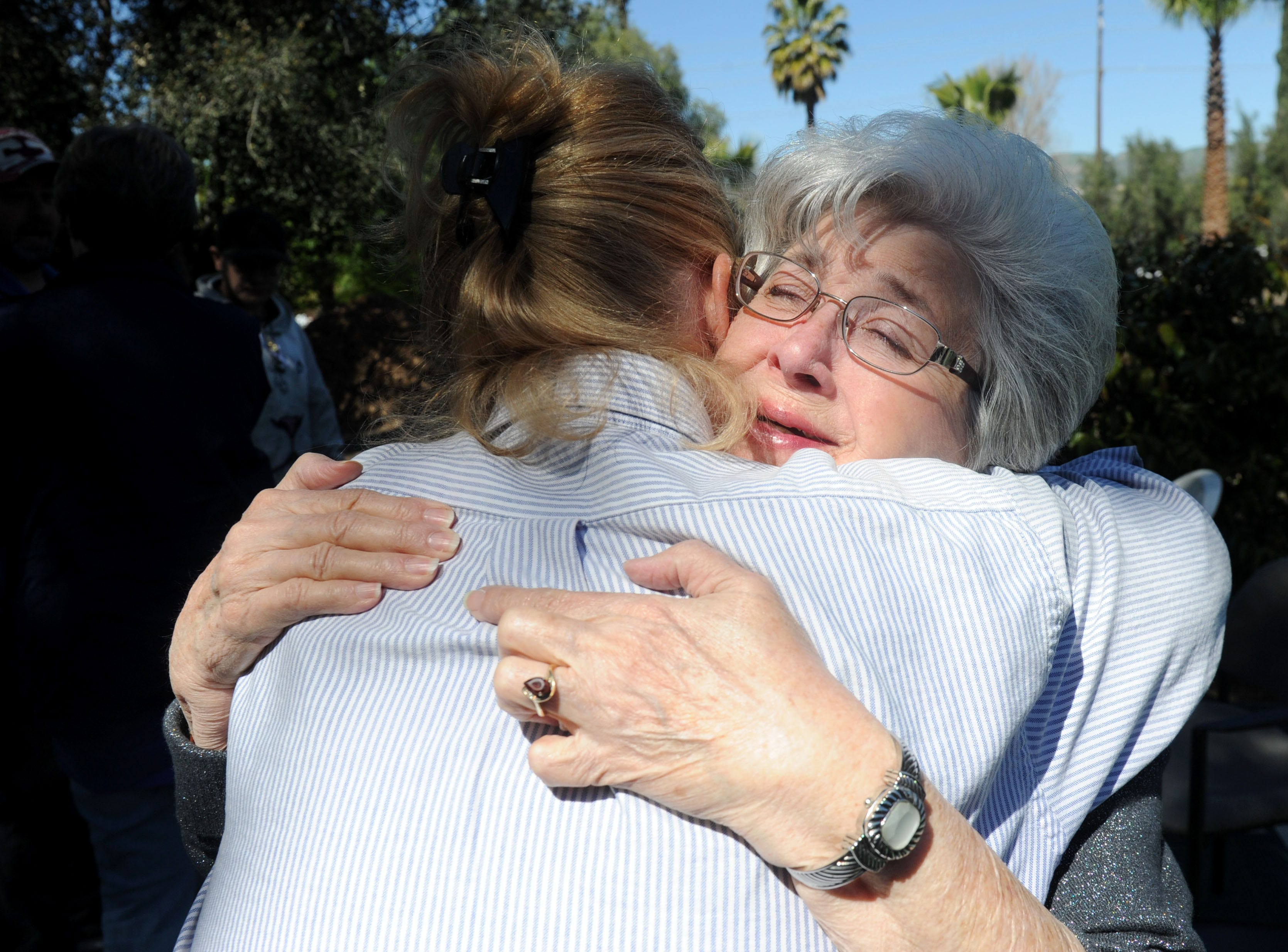 Sharon Heiser, a volunteer at the Simi Valley Samaritan Center, gets a hug from the Rev. Sarah Kitch of St. Francis of Assisi Episcopal Church. The women were among dozens of people at a memorial service Wednesday for Gerald Munyon.