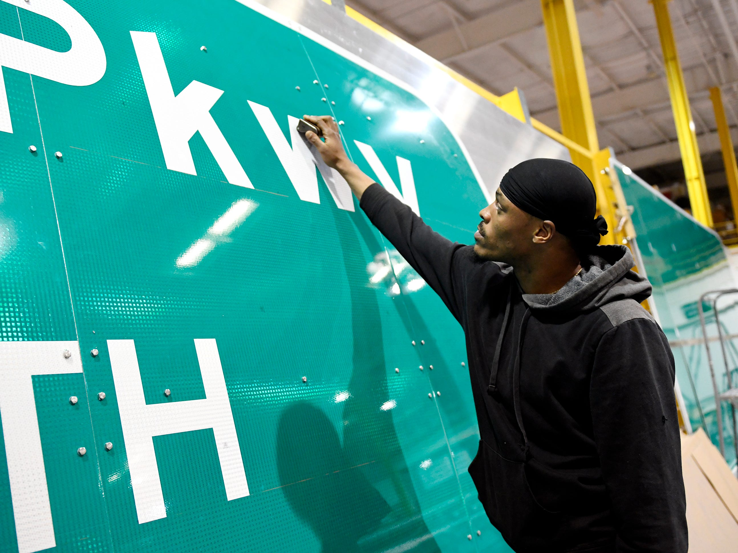 A Garden State Highway Products, Inc. employee works on a large highway sign on Tuesday, Mar. 12, 2019. The company also distributes a vast assortment of traffic safety and work zone construction products.
