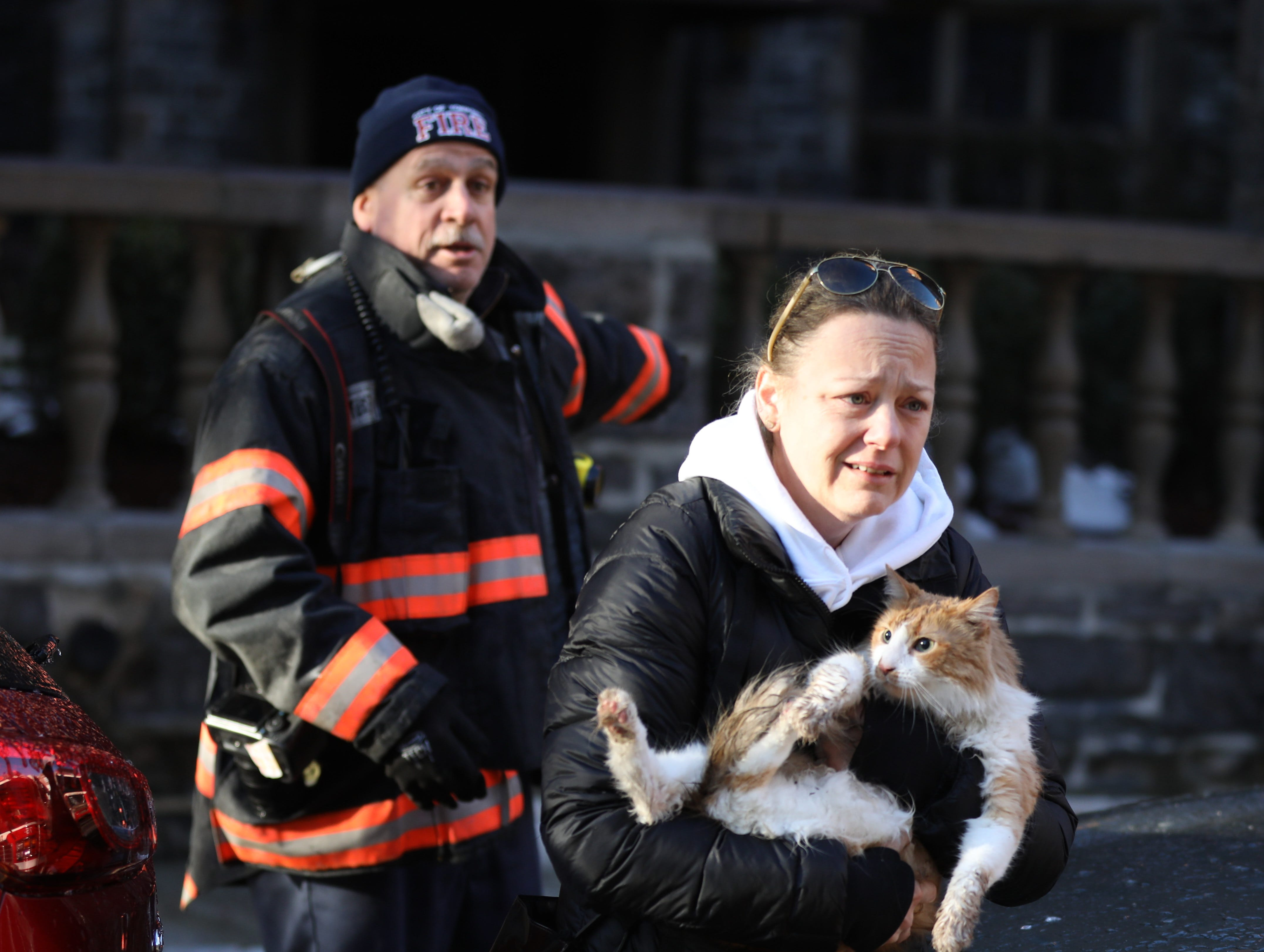 Paige Loonan retrieves her cat Dolche, with the help of Yonkers fire investigator Chris Leal, at 15 Parkview Avenue in Yonkers, March 13, 2019, the day after the general alarm fire fought by Yonkers firefighters and mutual aid companies.
