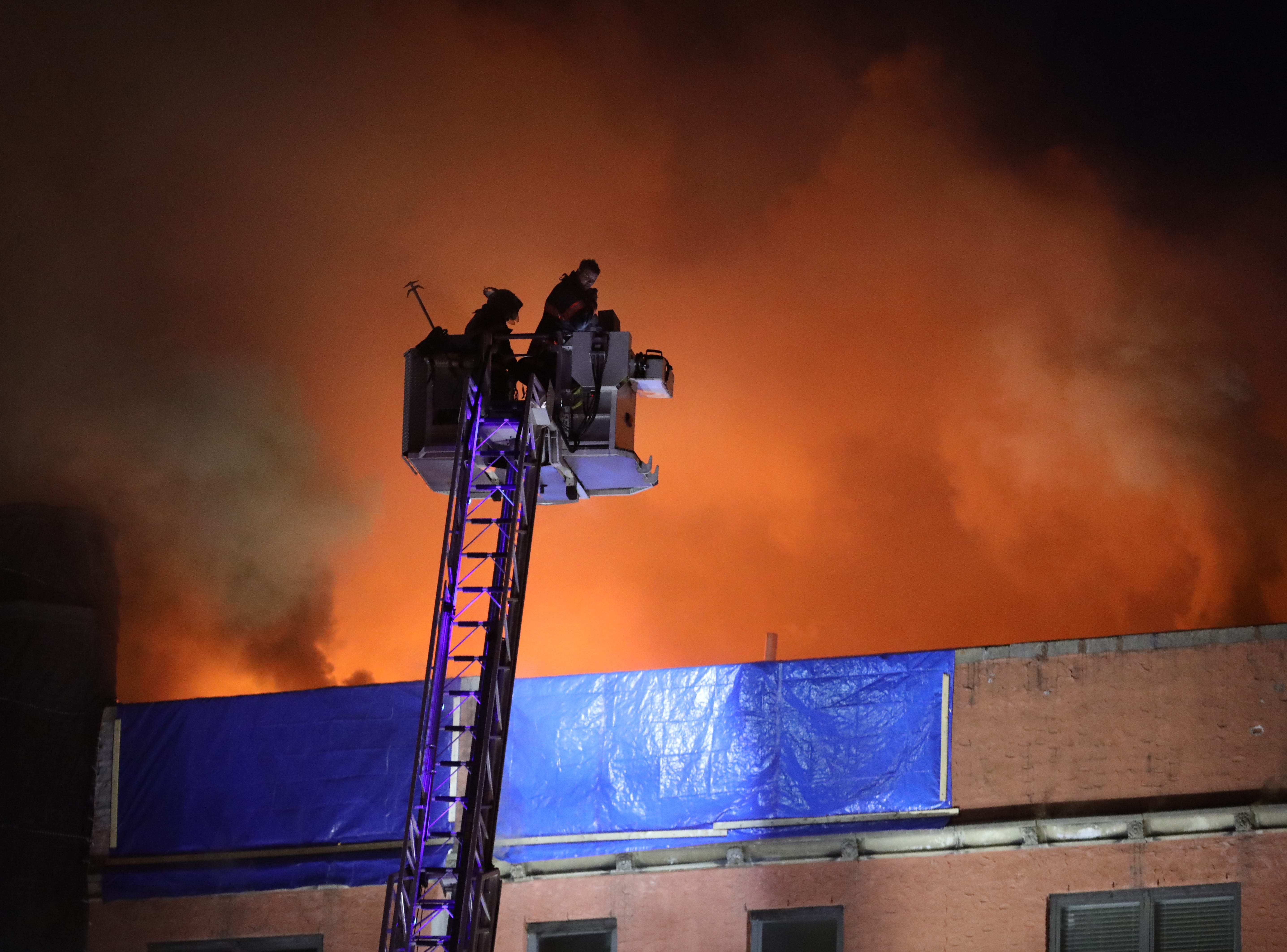 Yonkers firefighters in a tower ladder work as flames leap from the roof as Yonkers firefighters battle a four alarm fire at 15 Parkview Avenue in Yonkers, March 12, 2019.