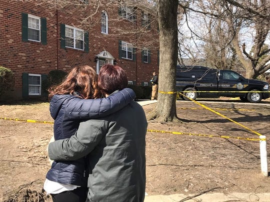 Jill McCormick and her mother, Andrea Bender, embrace as the bodies of Bender's sister and nephew are removed from the Stonehurst Gardens Apartments.