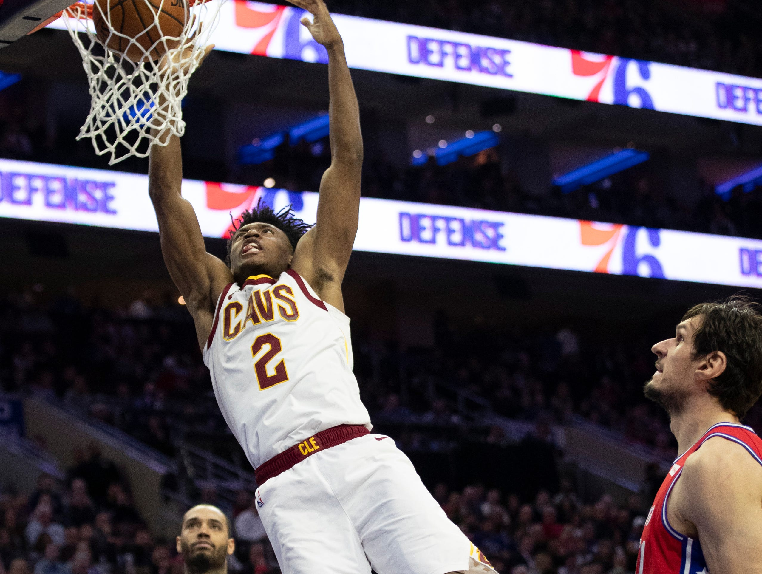 Cleveland Cavaliers' Collin Sexton, center, scores as Philadelphia 76ers' Mike Scott, left, and Boban Marjanovic, right, of Serbia, look on during the second half of an NBA basketball game, Tuesday, March 12, 2019, in Philadelphia. The 76ers won 106-99. (AP Photo/Chris Szagola)