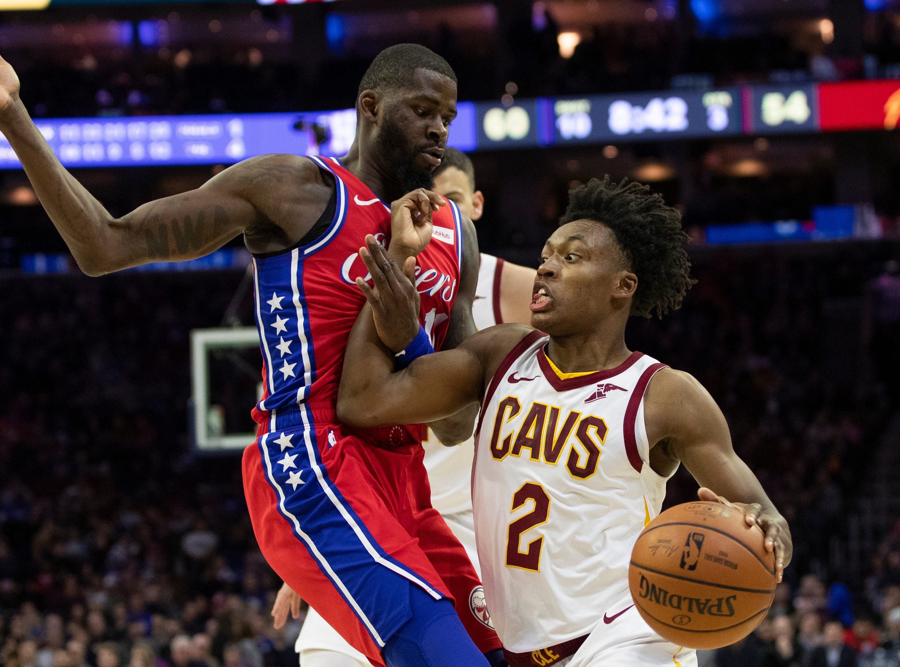 Cleveland Cavaliers' Collin Sexton, right, drives to the basket against Philadelphia 76ers' James Ennis III, left, during the second half of an NBA basketball game, Tuesday, March 12, 2019, in Philadelphia. The 76ers won 106-99. (AP Photo/Chris Szagola)