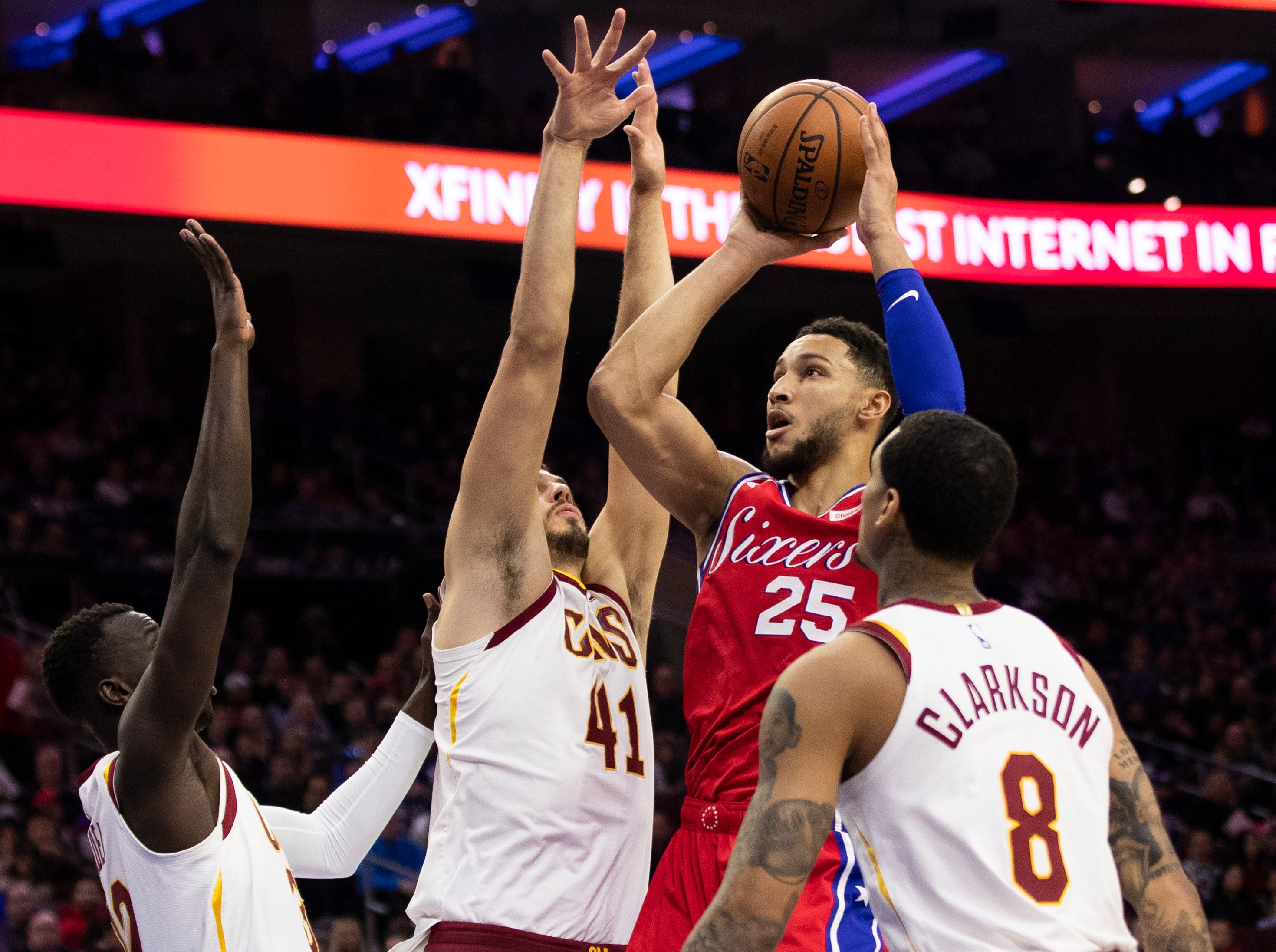 Philadelphia 76ers' Ben Simmons (25), of Australia, shoots against Cleveland Cavaliers' Deng Adel, left, of South Sudan, Ante Zizic (41), of Croatia, and Jordan Clarkson (8) during the first half of an NBA basketball game, Tuesday, March 12, 2019, in Philadelphia. The 76ers won 106-99. (AP Photo/Chris Szagola)