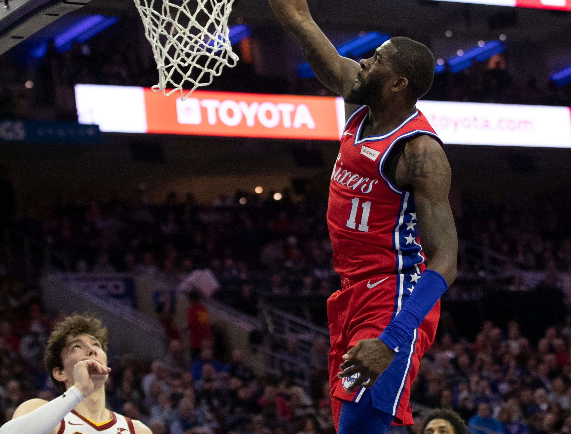 Philadelphia 76ers' James Ennis III, right, dunks the ball with Cleveland Cavaliers' Cedi Osman, left, of Turkey, looking on during the first half of an NBA basketball game, Tuesday, March 12, 2019, in Philadelphia. (AP Photo/Chris Szagola)