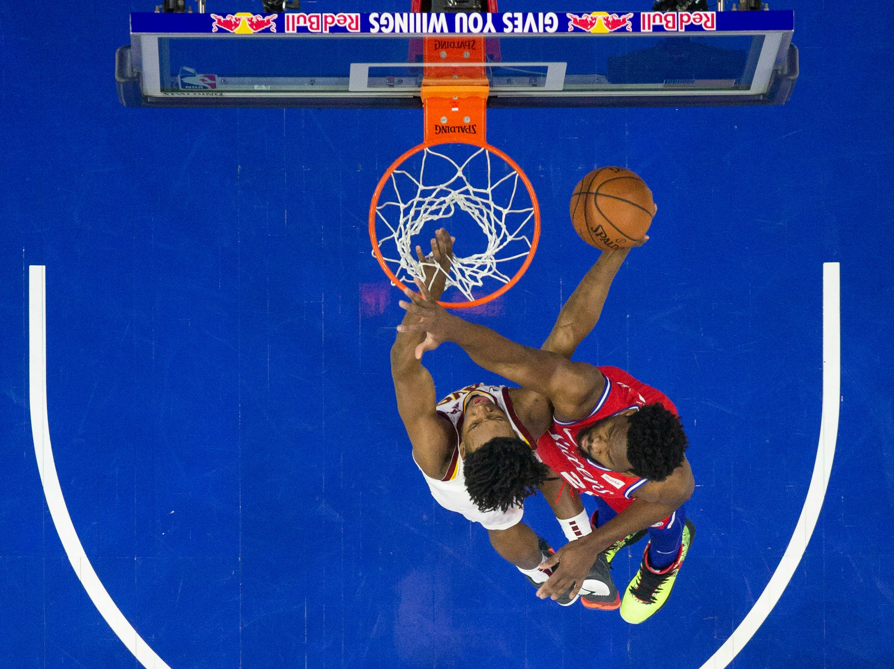 Cleveland Cavaliers' Collin Sexton, left, shoots against Philadelphia 76ers' Joel Embiid, right, of Cameroon, during the first half of an NBA basketball game, Tuesday, March 12, 2019, in Philadelphia. (AP Photo/Chris Szagola)