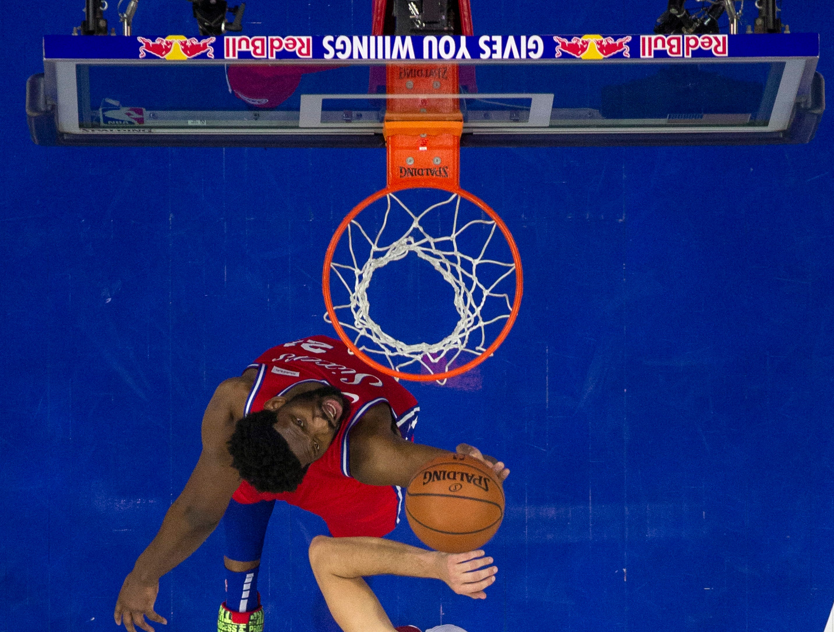 Philadelphia 76ers' Joel Embiid, left, of Cameroon, shoots with Cleveland Cavaliers' Ante Zizic, right, of Croatia, defending during the second half of an NBA basketball game, Tuesday, March 12, 2019, in Philadelphia. The 76ers won 106-99. (AP Photo/Chris Szagola)