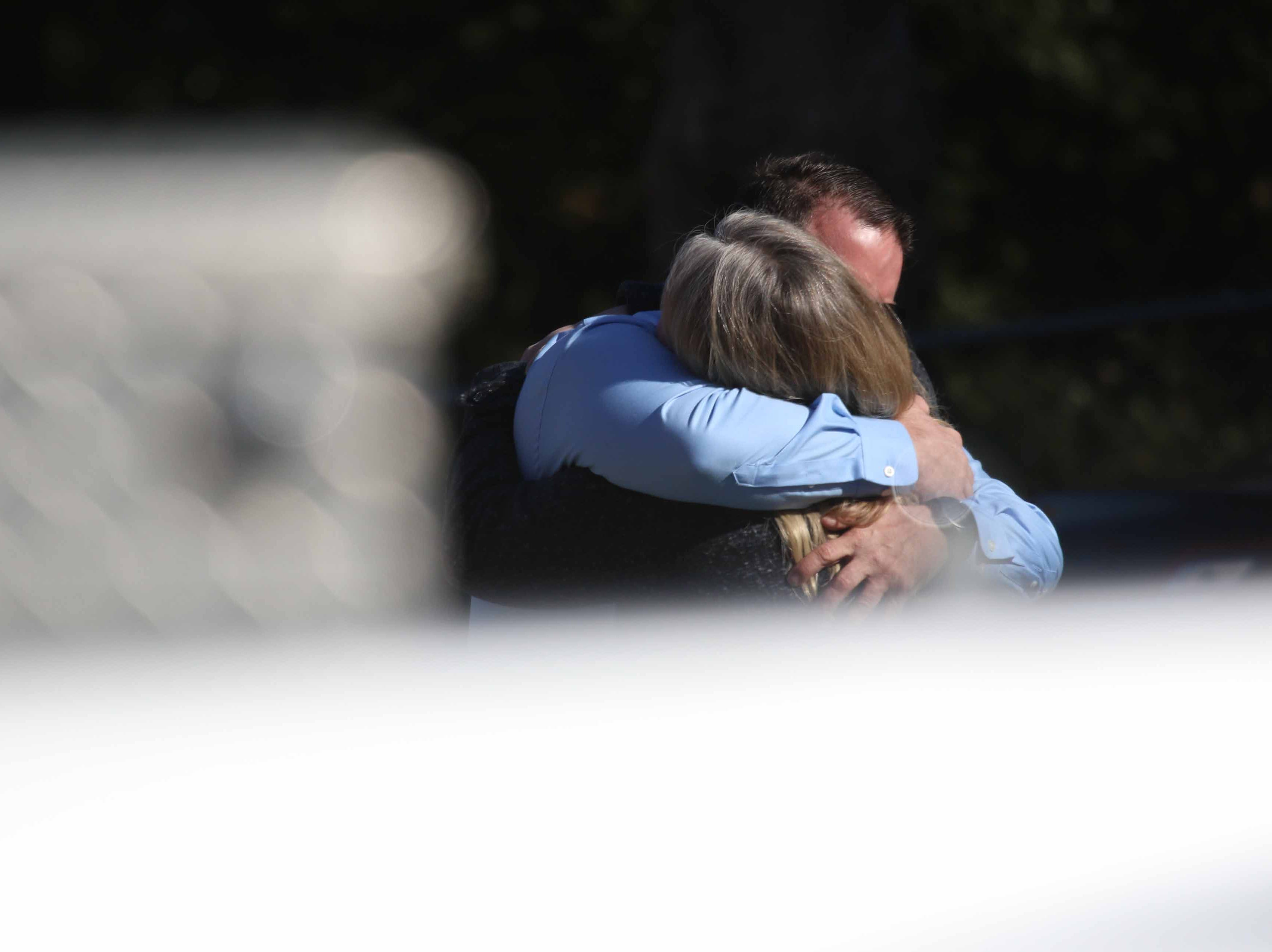 A man a woman embrace at the scene where police were investigating an apartment on 100 block of Richards Drive Wednesday morning after two people were found dead.
