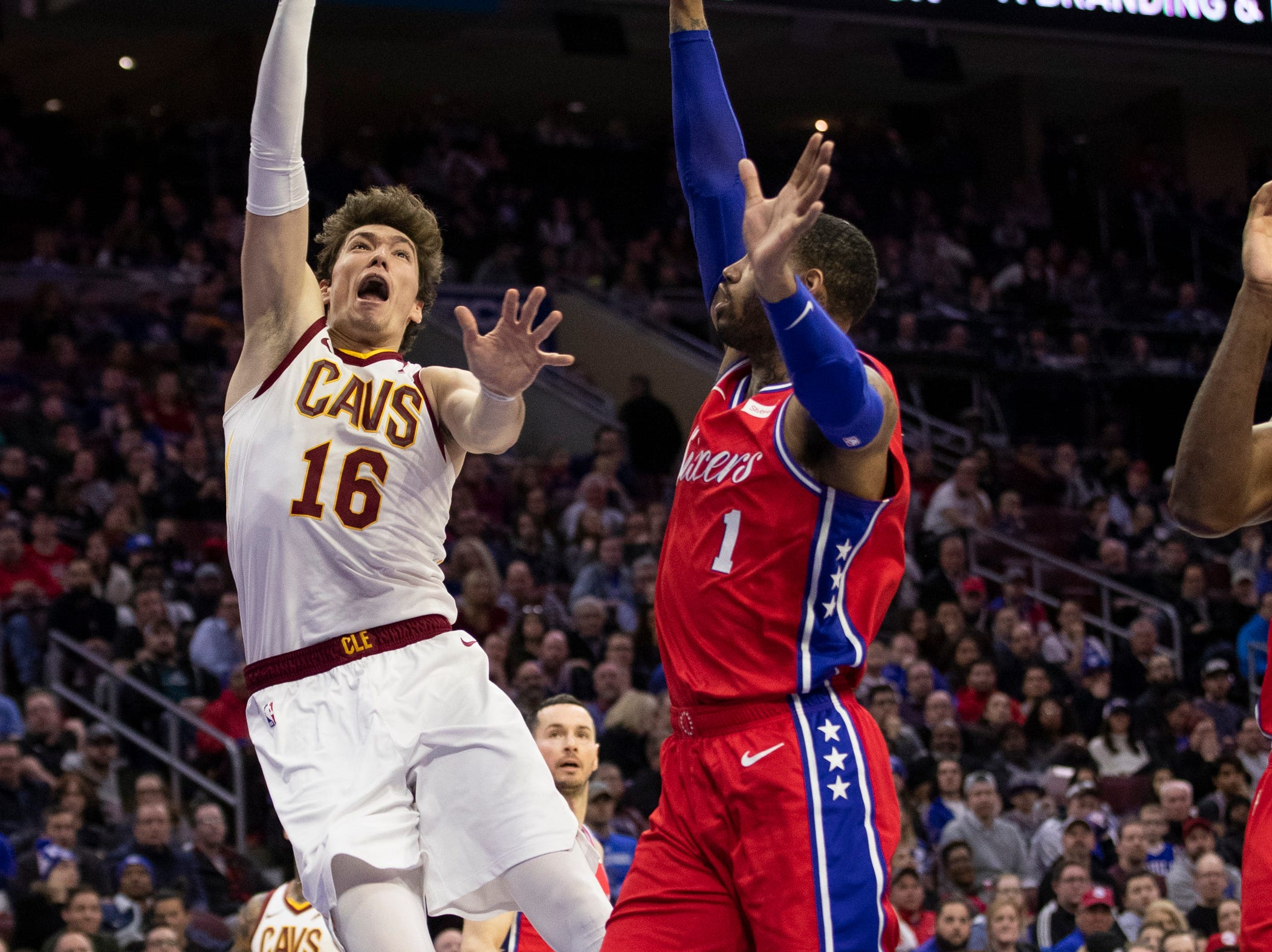 Cleveland Cavaliers' Cedi Osman, left, of Turkey, shoots with Philadelphia 76ers' Mike Scott, right, defending during the second half of an NBA basketball game, Tuesday, March 12, 2019, in Philadelphia. The 76ers won 106-99. (AP Photo/Chris Szagola)