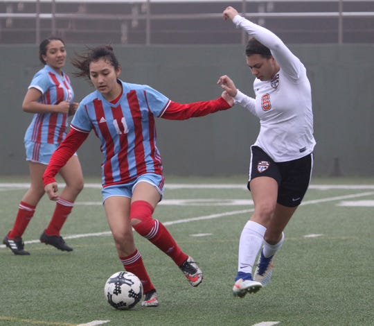 Hirschi's Jazmine Chavarria dribbles by Burkburnett's Raegan King Tuesday, March 12, 2019, at Memorial Stadium.