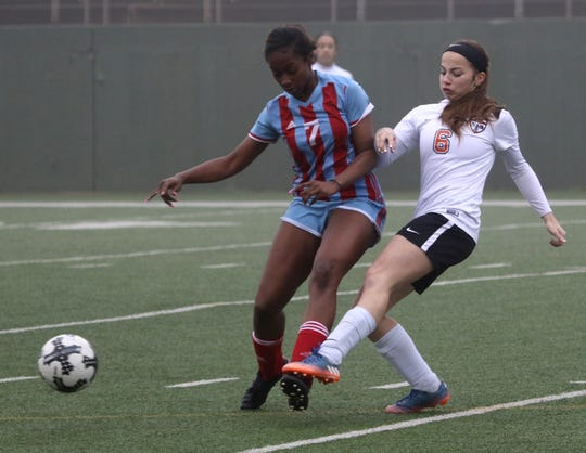 Burkburnett's Kanryn Major (6) passes by Hirschi's Skyy Lee Tuesday, March 12, 2019, at Memorial Stadium.