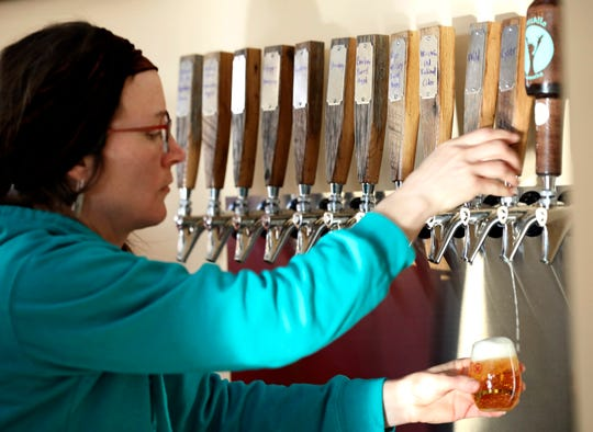 In this Friday, Feb. 8, 2019 photo, April Prusia draws a glass of cider for a customer at Brix Cider in Mount Horeb, Wis. Prusia also owns a farm near Blanchardville where she feeds her pigs pressed apples. They are then made into sausage that is on the menu at Brix. (Amber Arnold/Wisconsin State Journal via AP)
