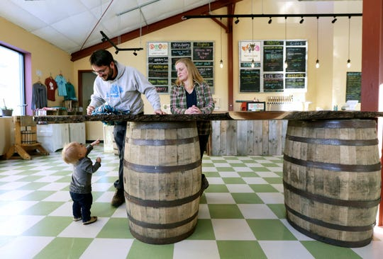 In this Friday, Feb. 8, 2019 photo, Matt and Marie Raboin watch their 1-year-old daughter, Vera, toddle around the floor at Brix Cider in Mount Horeb, Wis. The pub serves up hard cider from apples harvested from 18 farms along with food, much of it grown or produced in the area. The table top that sits on top of the barrels was from a walnut tree on the Raboins' property south of Barneveld. (Amber Arnold/Wisconsin State Journal via AP)