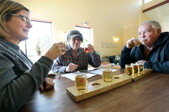 In this Friday, Feb. 8, 2019 photo, Lisa Venden, left, with her husband, Roger, right, and Sandy Strommen, all of Mount Horeb, sample cider at Brix Cider in Mount Horeb, Wis. (Amber Arnold/Wisconsin State Journal via AP)