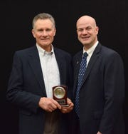 R. Paul Burh (left) of Viroqua is presented the Marlowe Nelson Distinguished Service Award by Corey Geiger.
